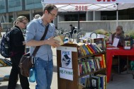 A student picks up a free book at the Marriott Library's Earth Fest booth.