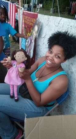 Demarcus Jones Books creator plays with the Zoli Zi doll.