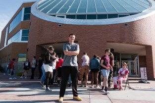 """Josh Stier poses in front of SUU Sherratt Library as a group of zombies gather behind him. Participating in the """"Walking Dead Escape"""" chase or be chased event on Tuesday, September 19th. Photo courtesy of photo journalist Morgan Barton."""