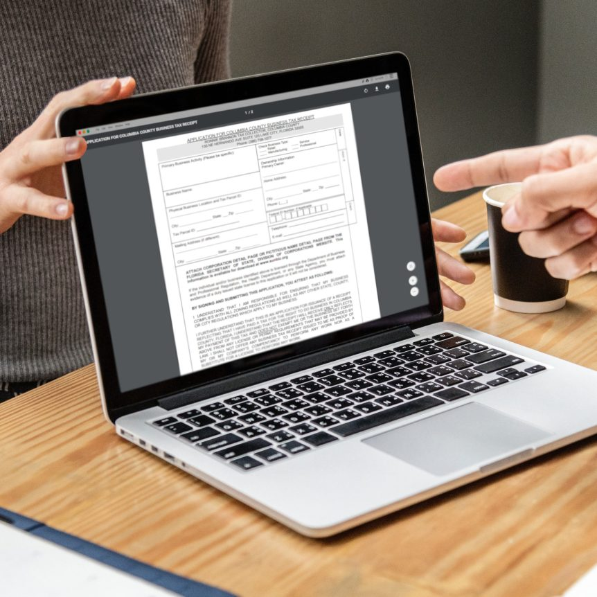 A man pointing to a laptop screen with a Florida tax form on it