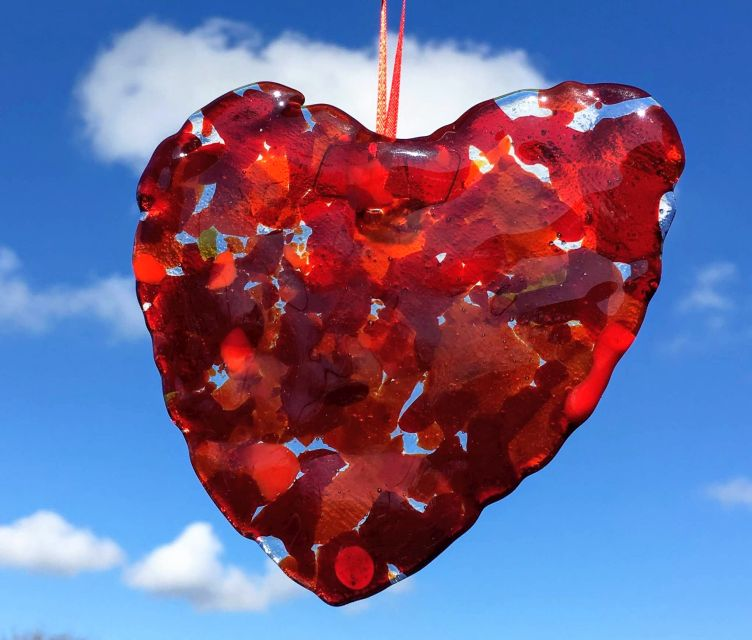 Glass ornament with encased red flakes like confetti shown against a blue sky