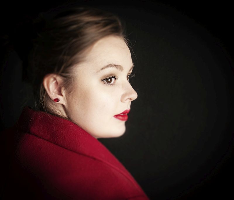 Red earing on model with matching red lipstick and coat