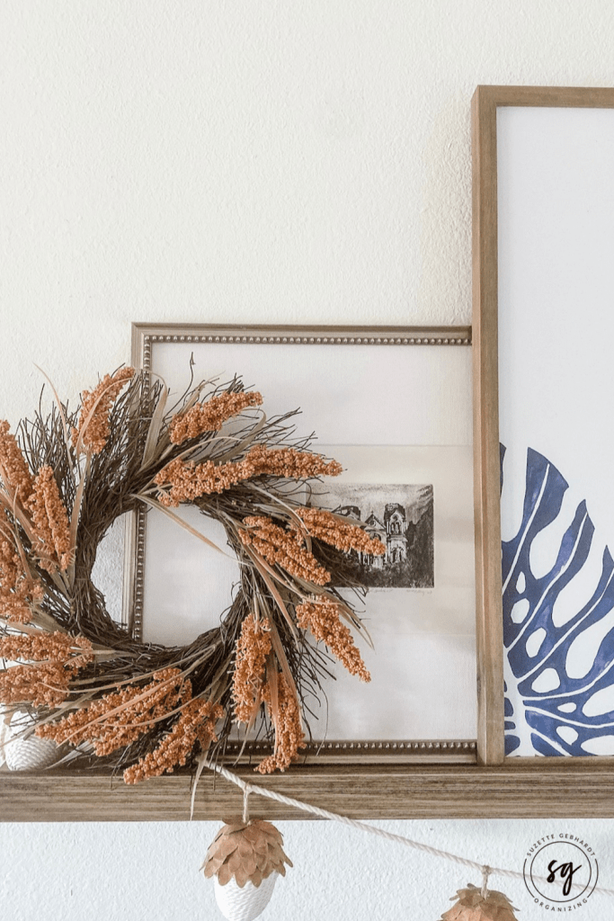 Holiday decorating idea: layer a fall wreath on top of existing photo ledge display.