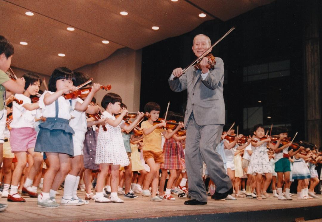 Dr Suzuki playing violin with children