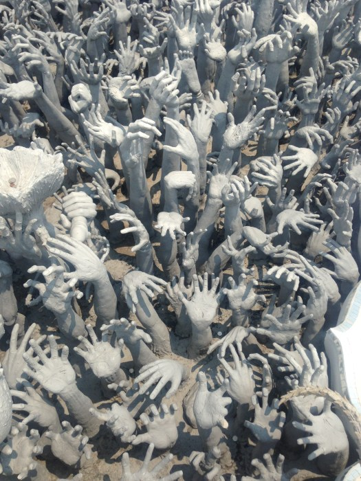 Grey stone hands reaching up from the group in a creepy