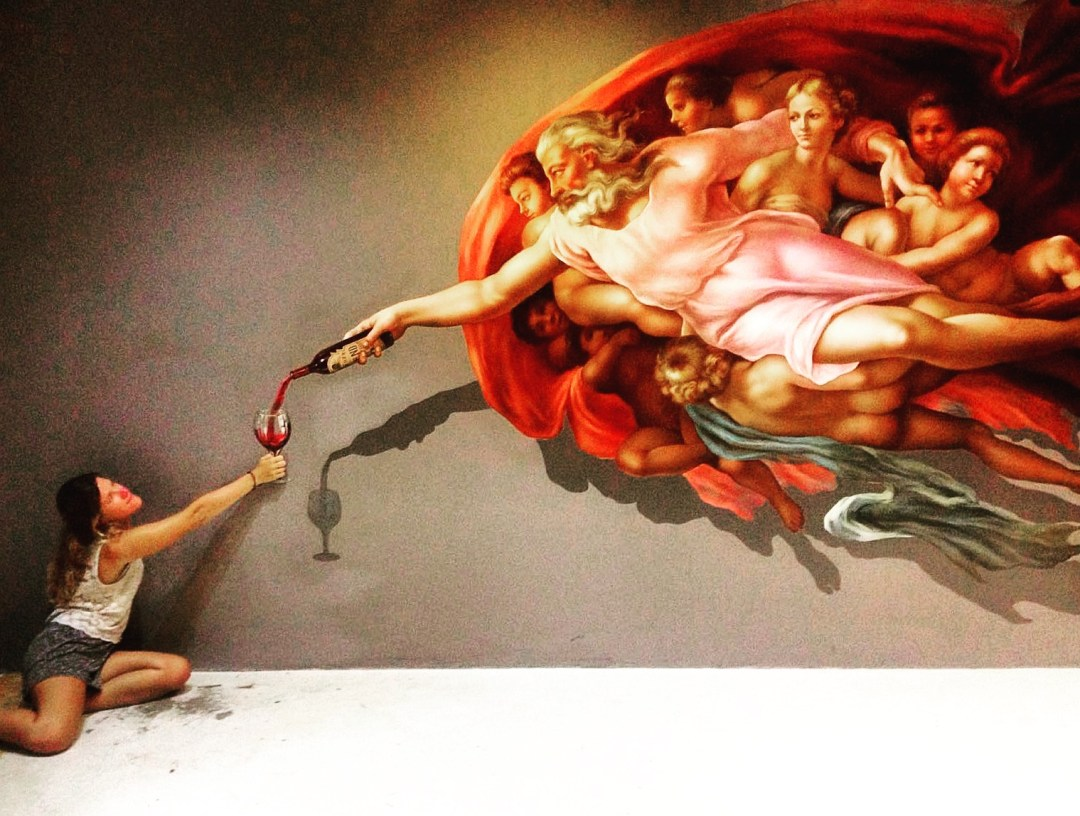 woman poses with immersive art work depicting the creation of adam with a wineglass