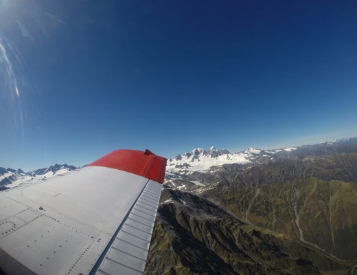 plane wing with snowy mountain peaks in new zealand