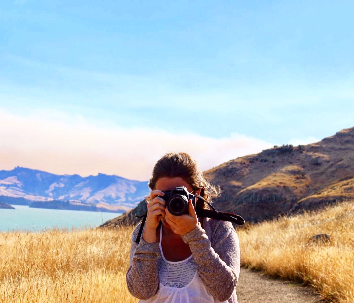 Girl pointing a camera at the photographer with colourful mountain scenery behind