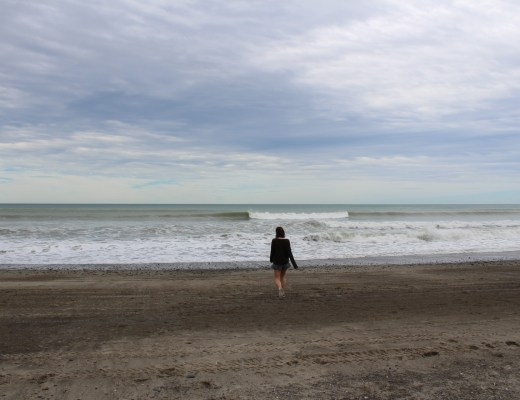 woman walks along sandy new zealand beach on storm day