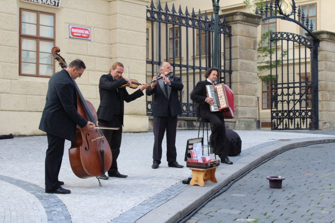 Beautiful quartet playing cheerful music to the tourists outside the castle entrance in Prague