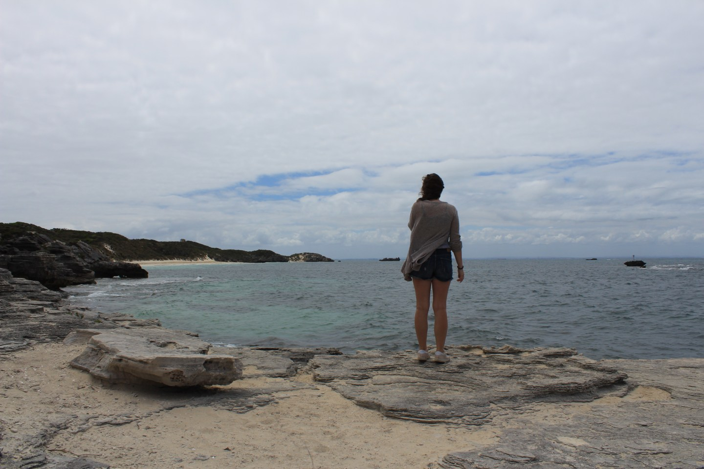 Girl stands on rocks overlooking the coast with overcast sky and sea