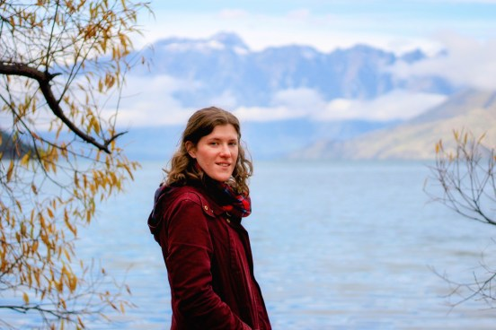 Girl faces camera in a red coat with mountain and lake views of Queenstown New Zealand behind