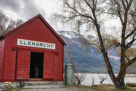 Red boatshed in Glenorchy New Zealand stands out against snow-capped mountains and lake
