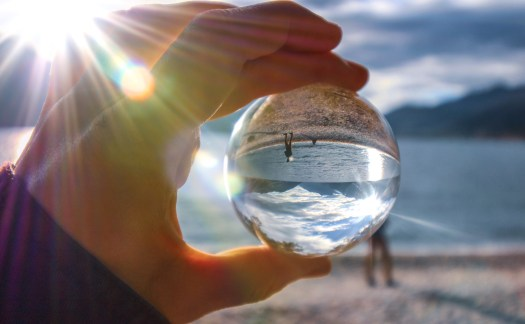 Holding a glass sphere an inverted photo of a sunset looking across the lake and mountains in New Zealand