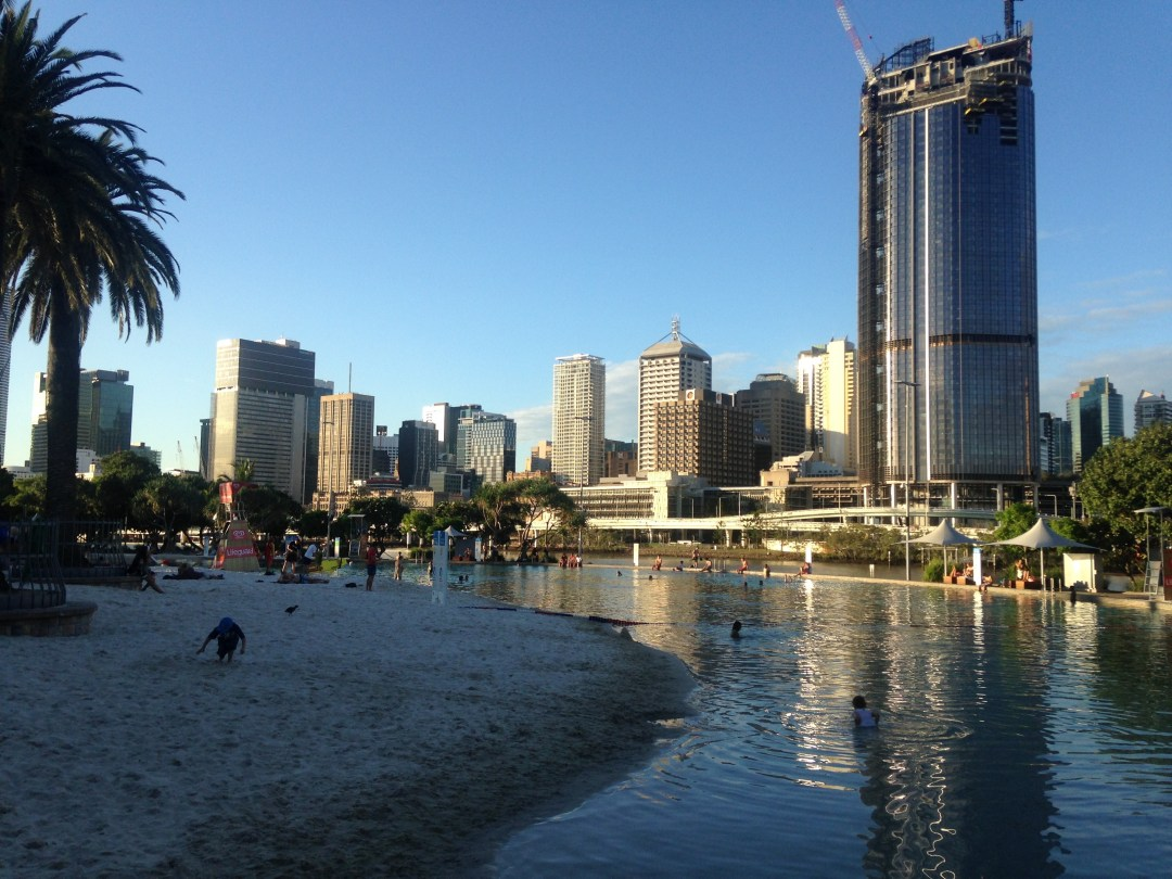 The sun sets over Brisbane lagoon with calm paddling waters and a man made beach overlooking a cityscape view