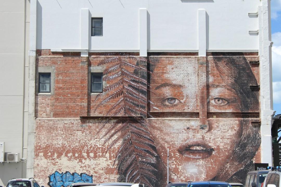 Street art in Christchurch depicting a woman and a fern leaf on a brick wall