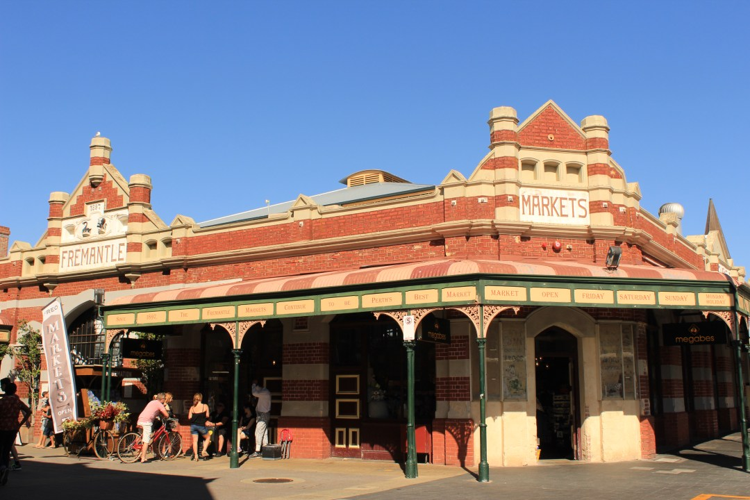 Blue skies behind Fremantle Market - a low brick building with visitors outside