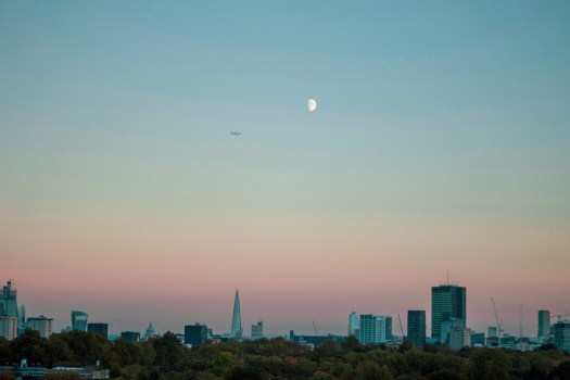 Plane flies over London at sunset