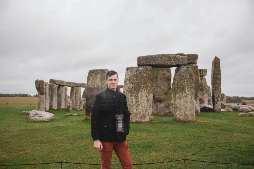 Man smiles to camera standing in front of Stonehenge in the rain