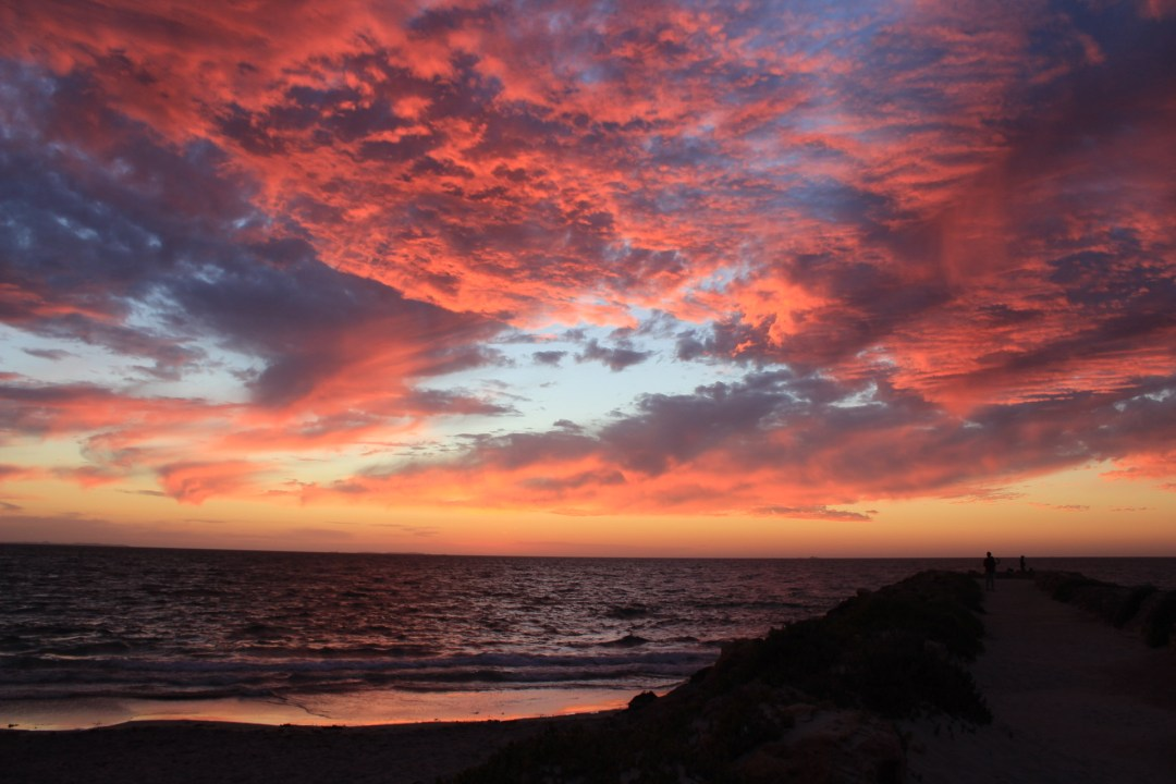 Bright pink and purple clouds of a sunset over the beach and sandy pier