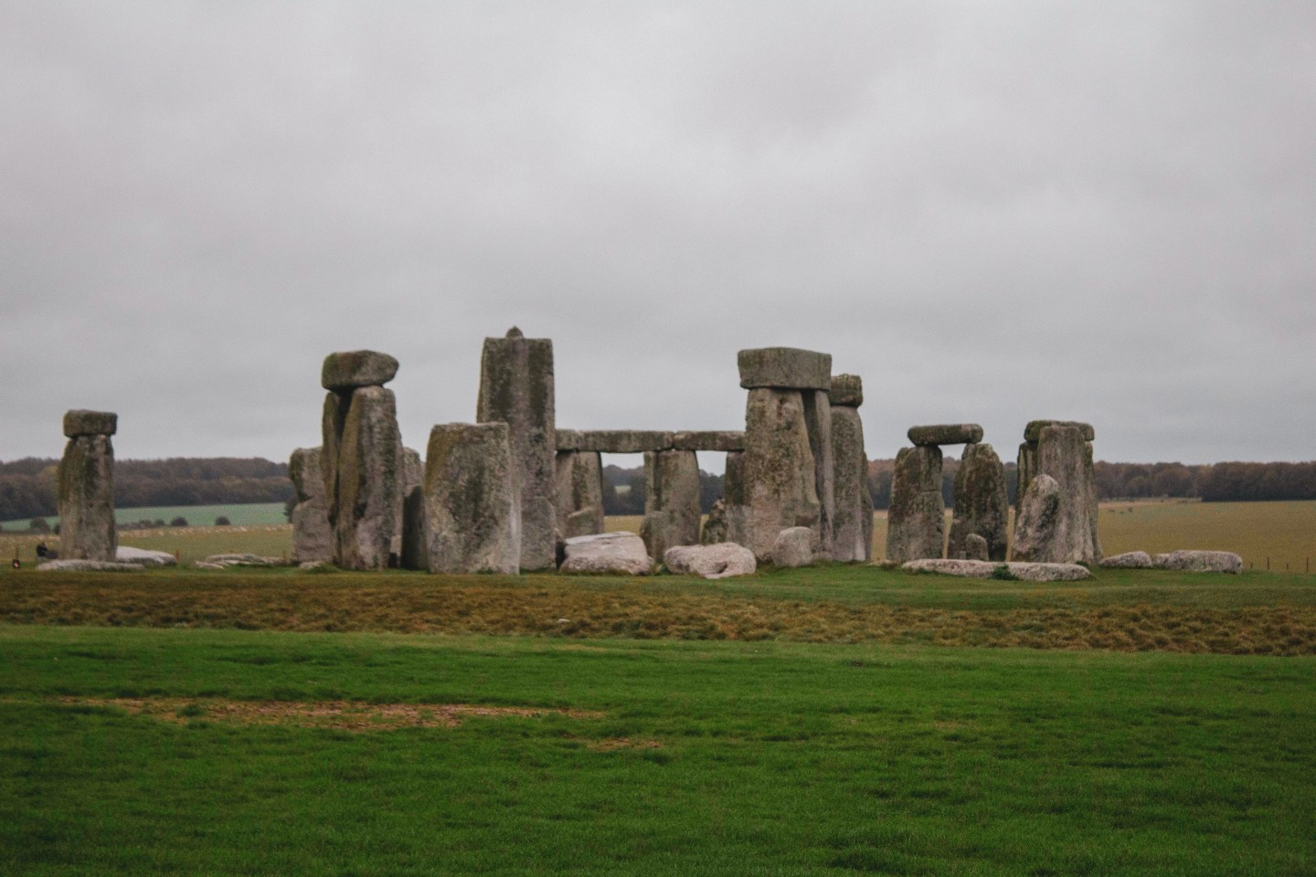 Stonehenge on a cloudy day with green fields surrounding