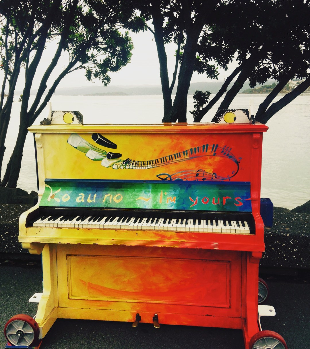 brightly painted piano stands in front of a moody Wellington harbour