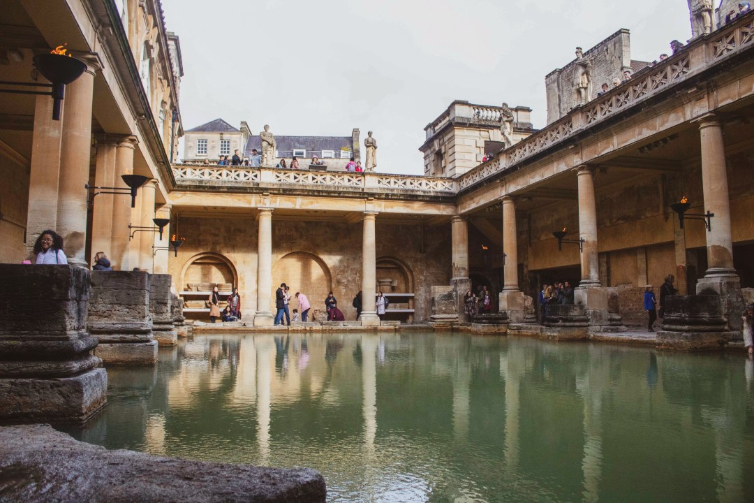 Green waters of the Roman Bath with yellow Bath stone all around and pillars supporting flaming beacons