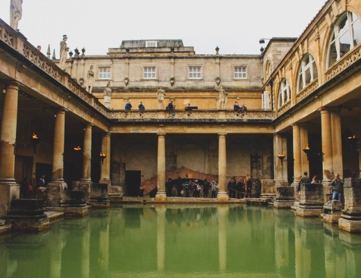 Reflection of green waters surrounded by old pillars and stone walls at the Roman Baths in Bath
