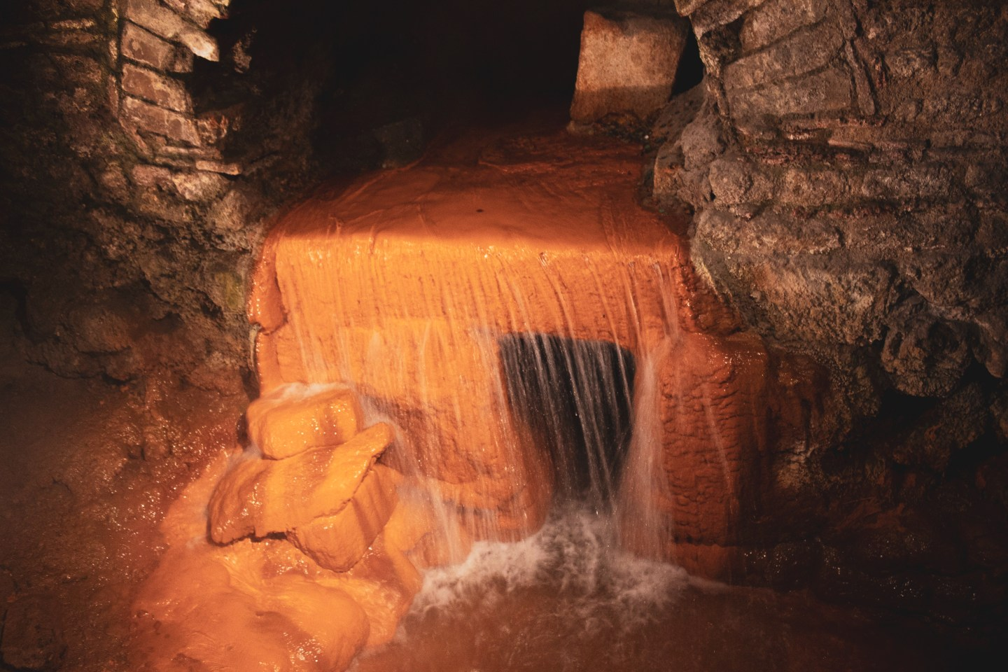 Water gushes from a tunnel with steam rising from it