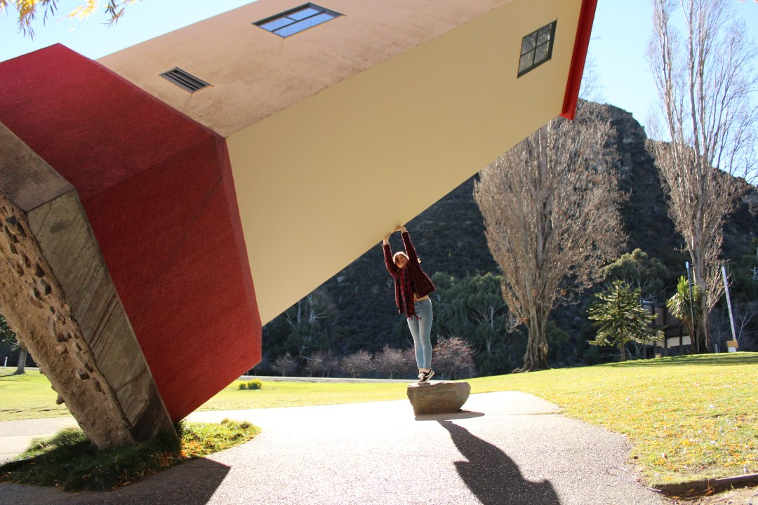 Girl pretends to hold up illusory of leaning building in New Zealand