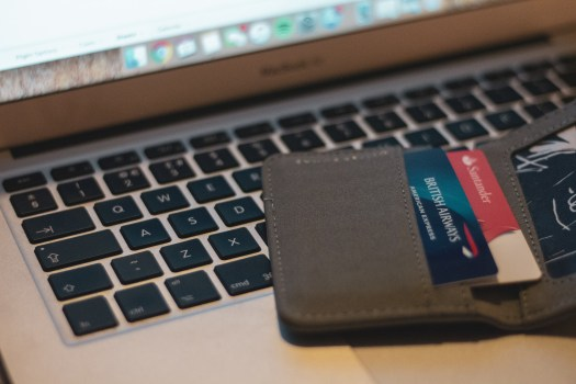open purse with credit card on laptop keyboard