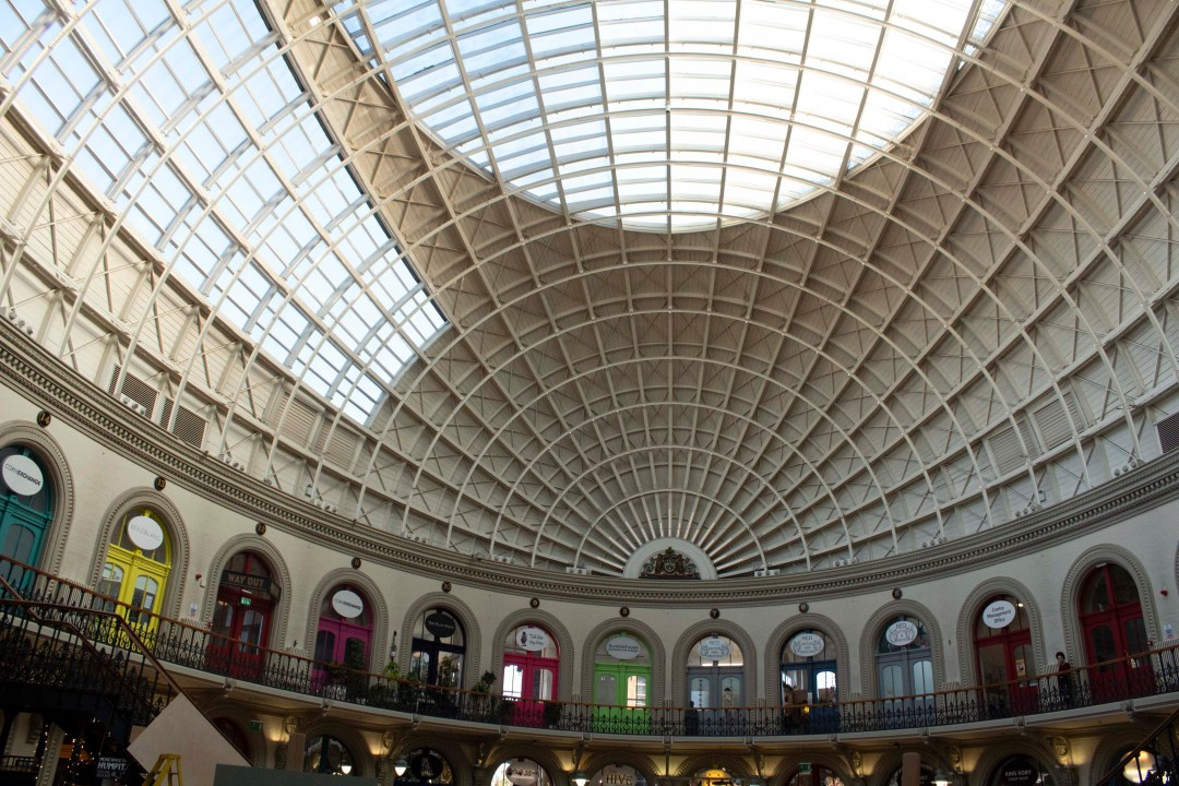 Inside Leeds Corn Exchange with coloured shops and glass dome roof