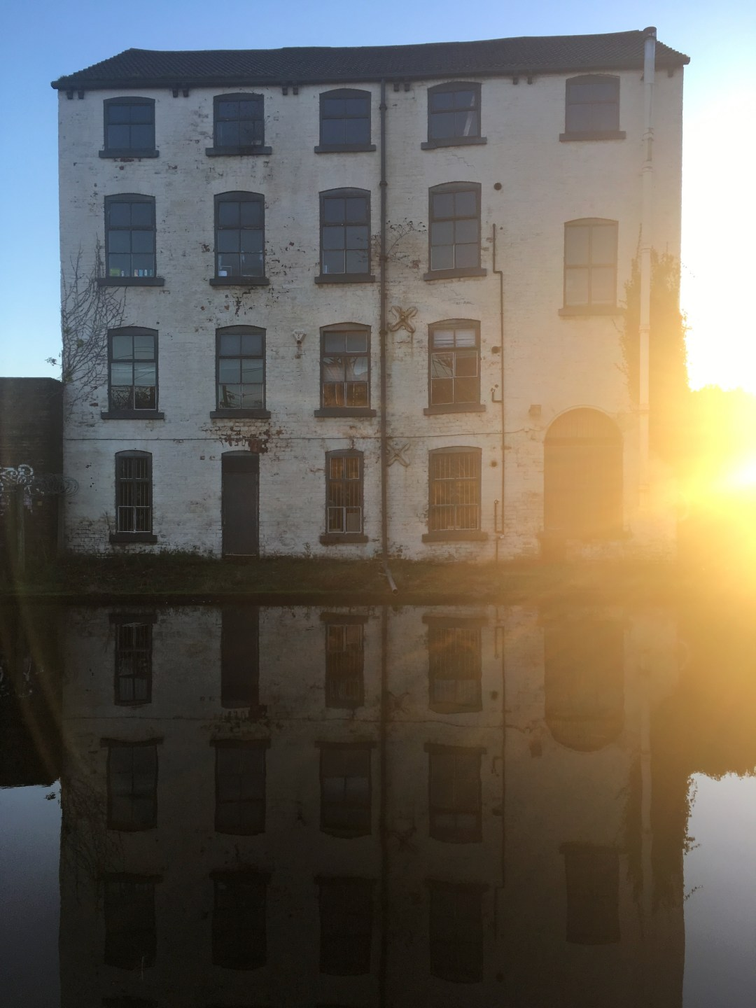 Sunset flares from behind abandoned building sitting on a river bank in Leeds