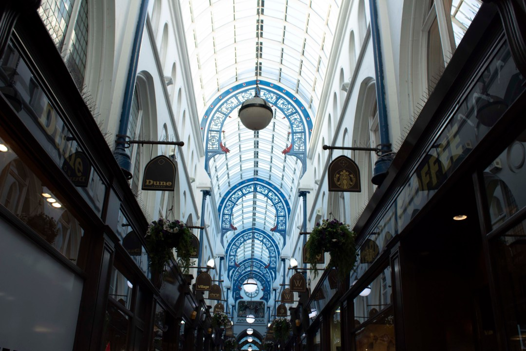 Shopping arcade in Leeds with blue arches and glass ceiling