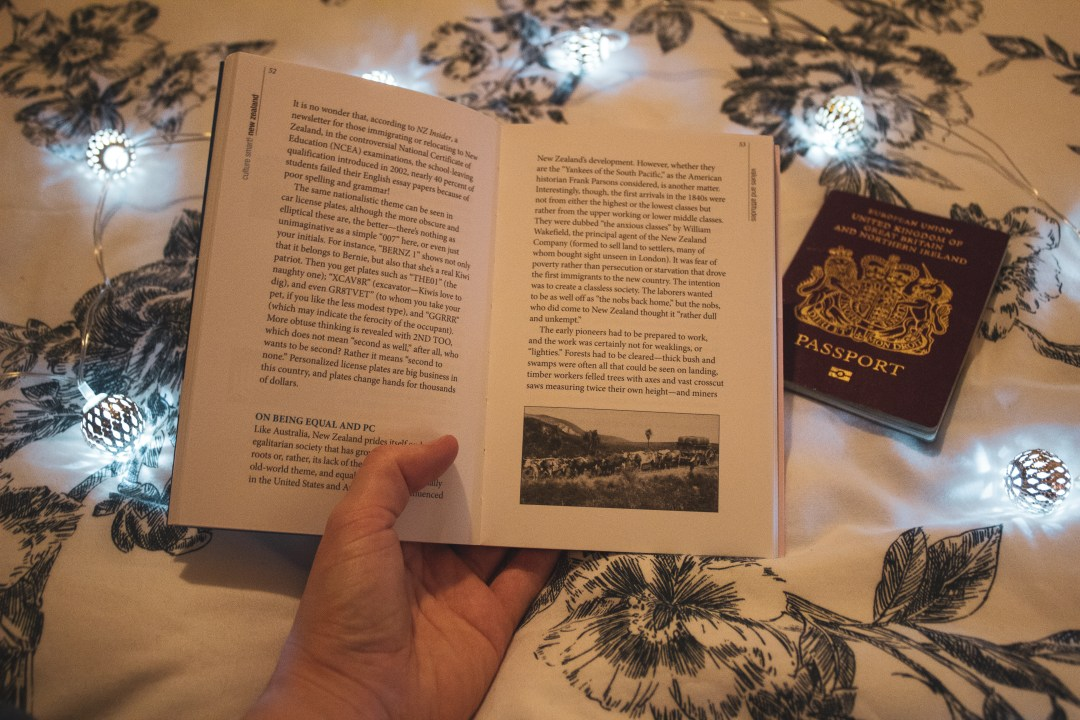 holding open book with passport
