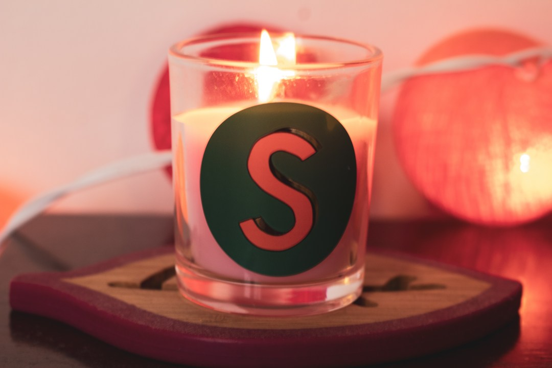 candle with S on it burns in front of lights