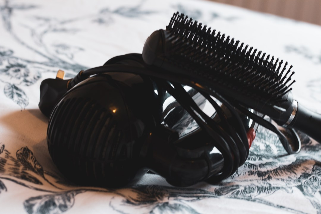 hairdryer and hair brush on bed