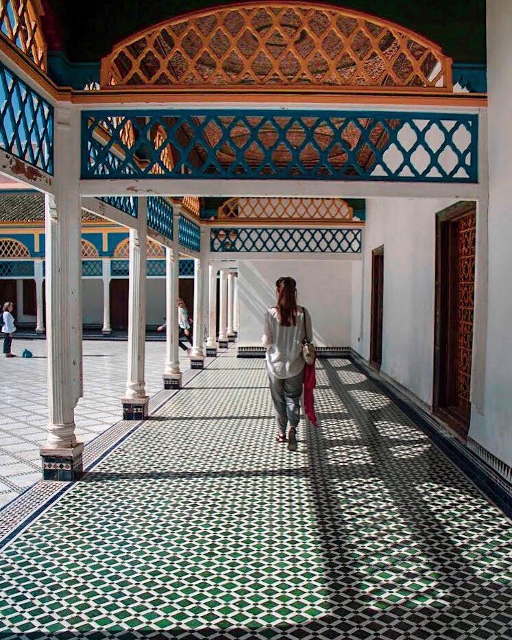 woman walks down moroccan courtyard