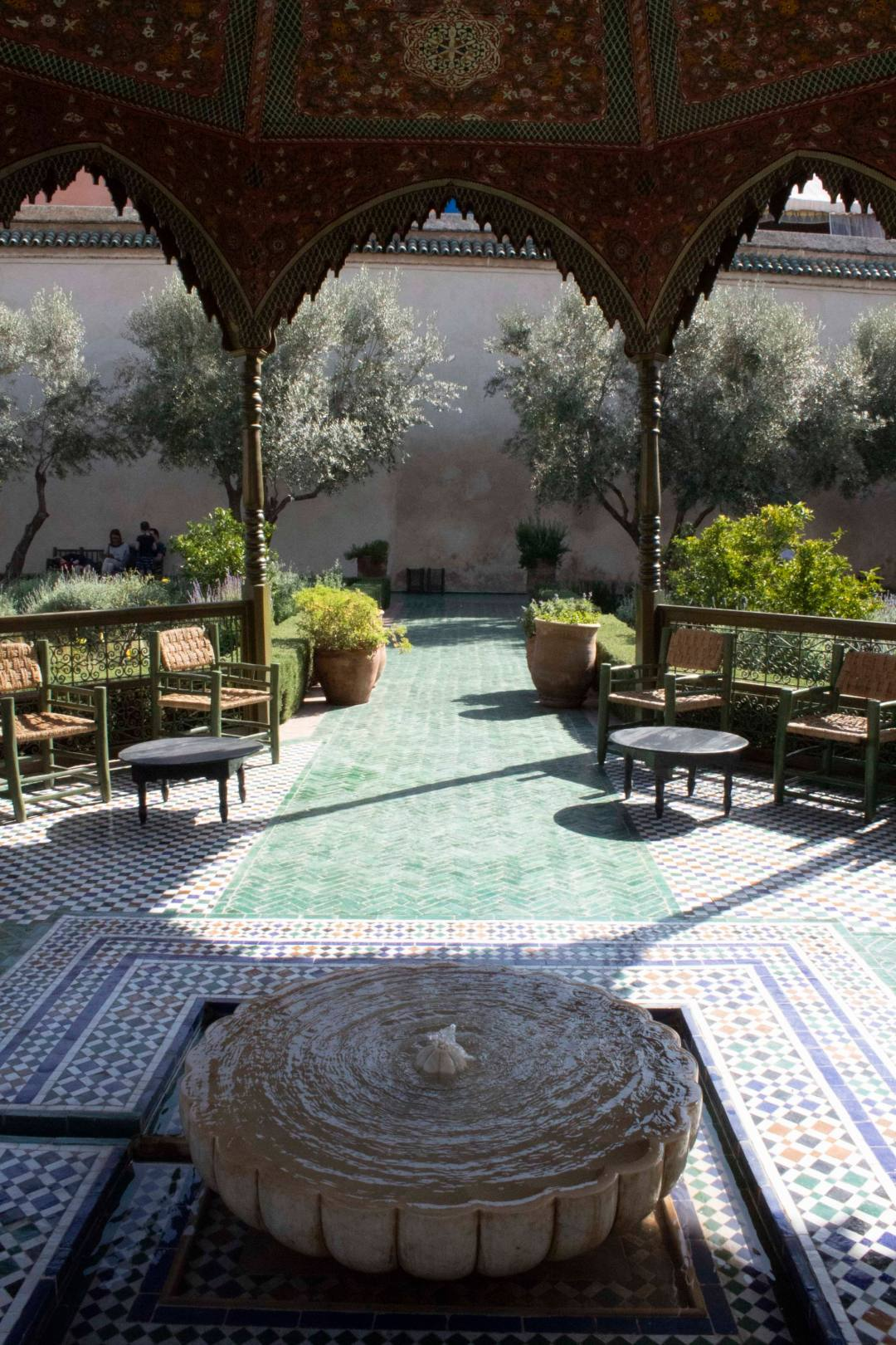 bubbling fountain and covered seating in tiled garden