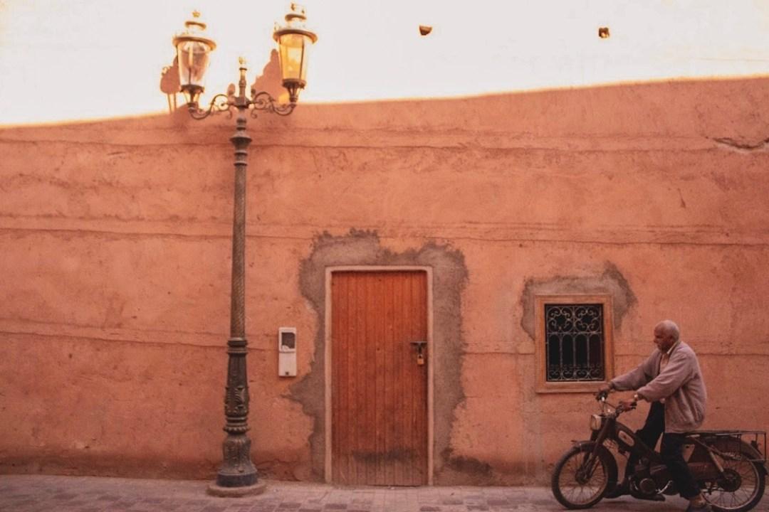 man rides bike past door and wall in Marrakech