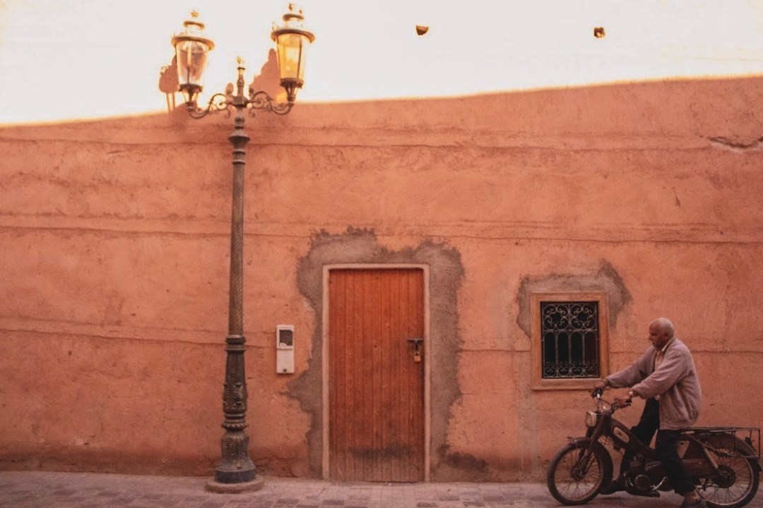 man rides bike past door and wall in Marrakech