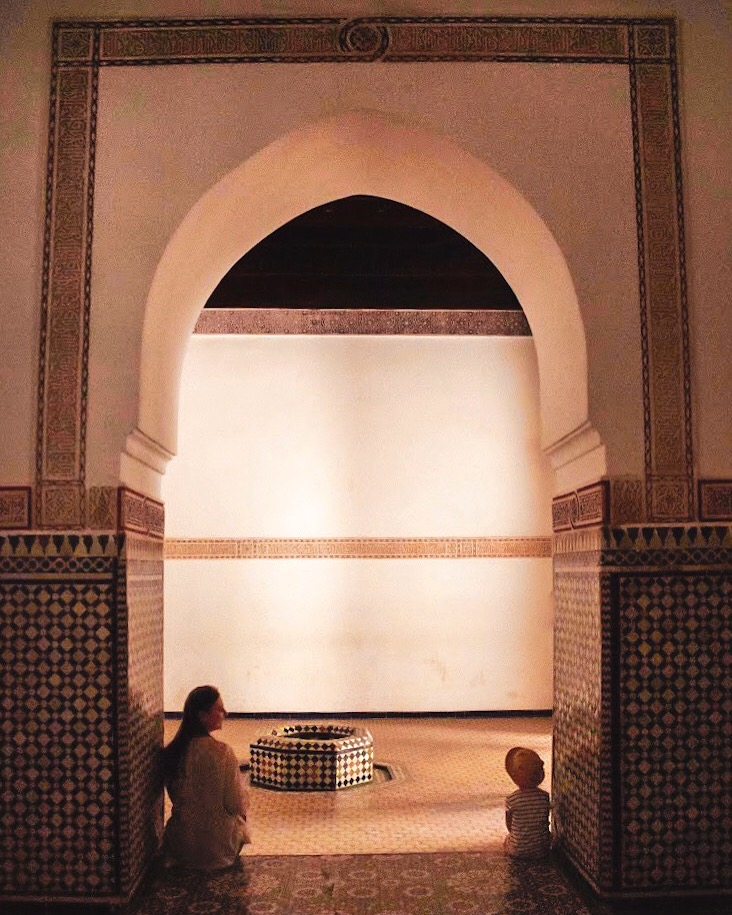 woman and girl sit on step inside Bahia Palace archway