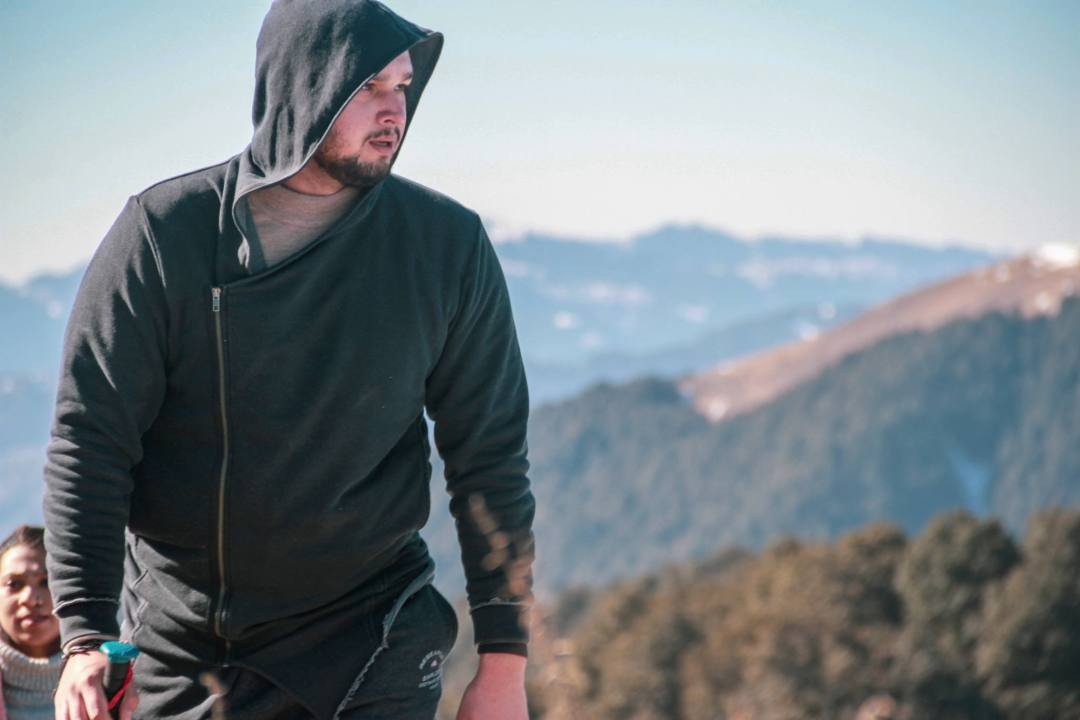 man hikes in warm attire with mountains behind
