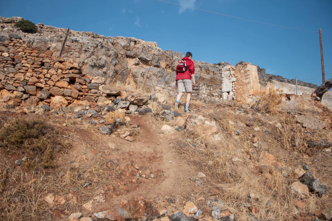 man walks up pathway alongside a wall to reach tomb of Kleoboulos lindos