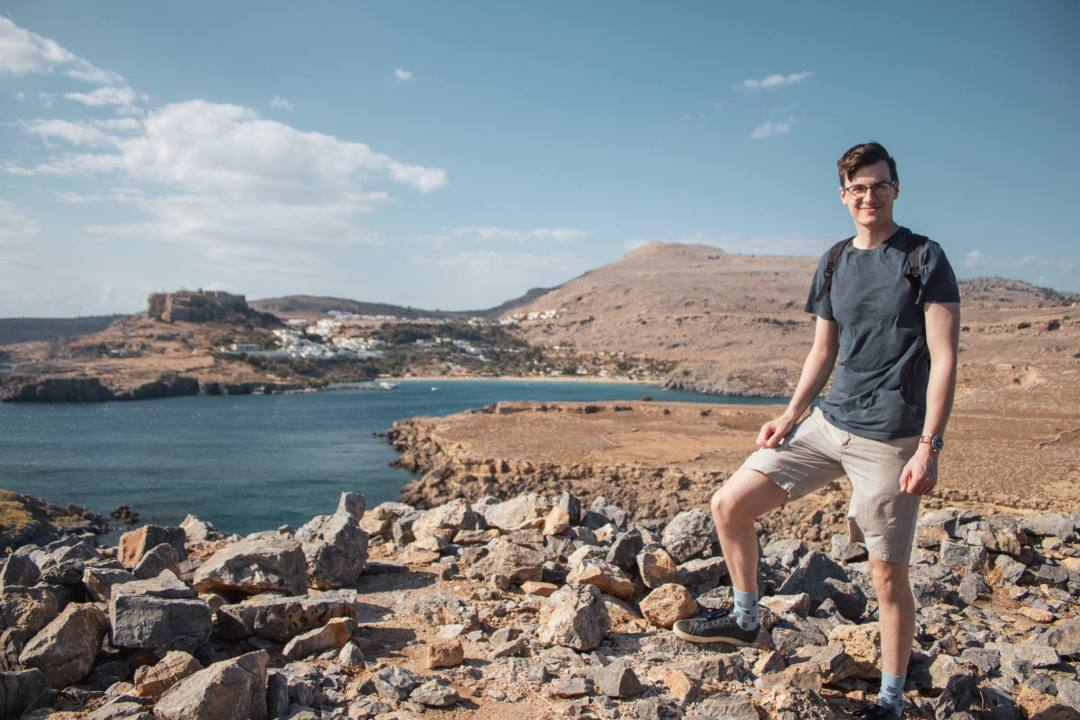 man posts in front of lindos acropolis and village landscape