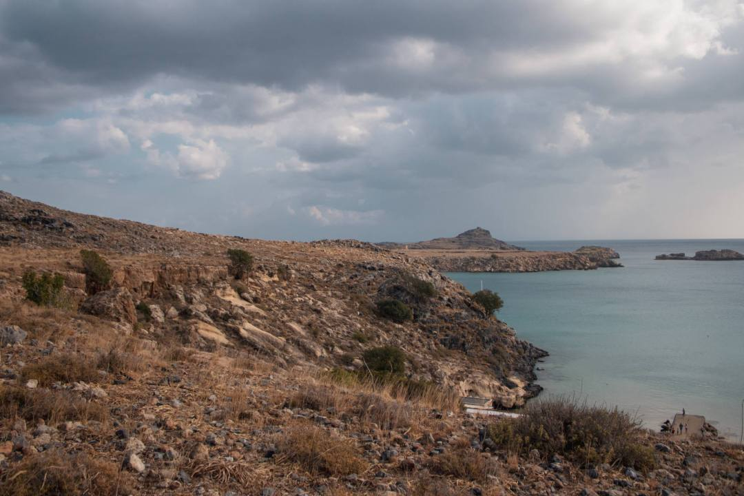 view of rocky coastal walk lindos with cloudy sky