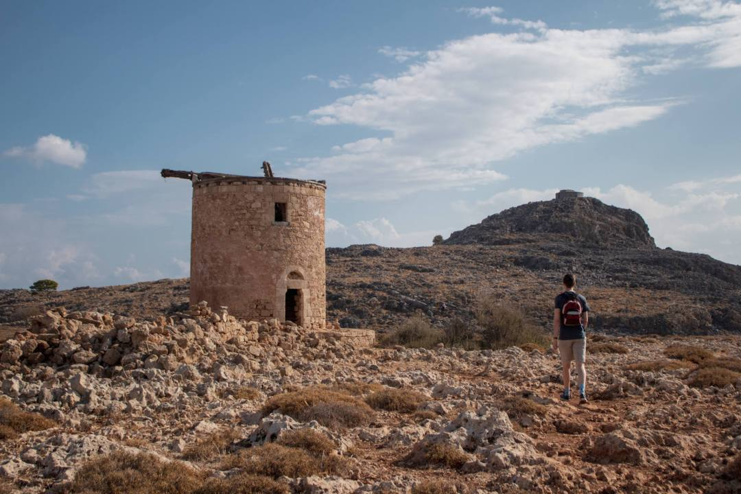 man stands next to old windmill ruins in lindos
