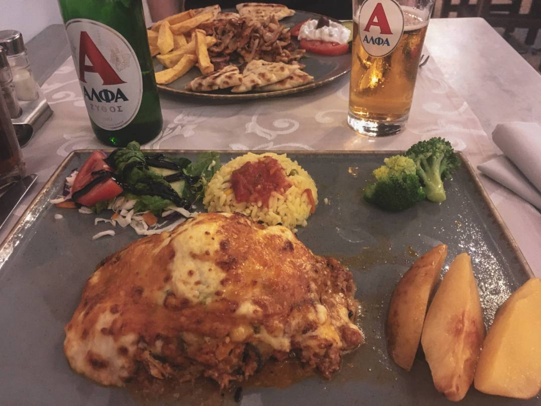 Greek food on plate with bottle of beer
