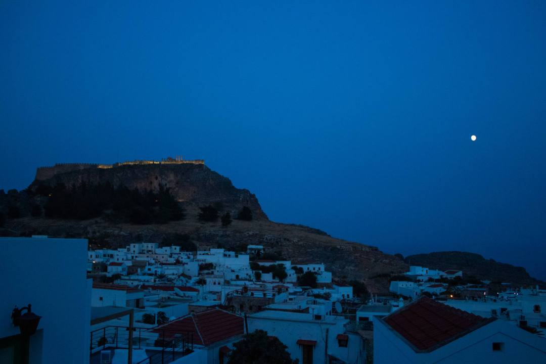 blue sunset sky and moon behind lindos village and acropolis on hill