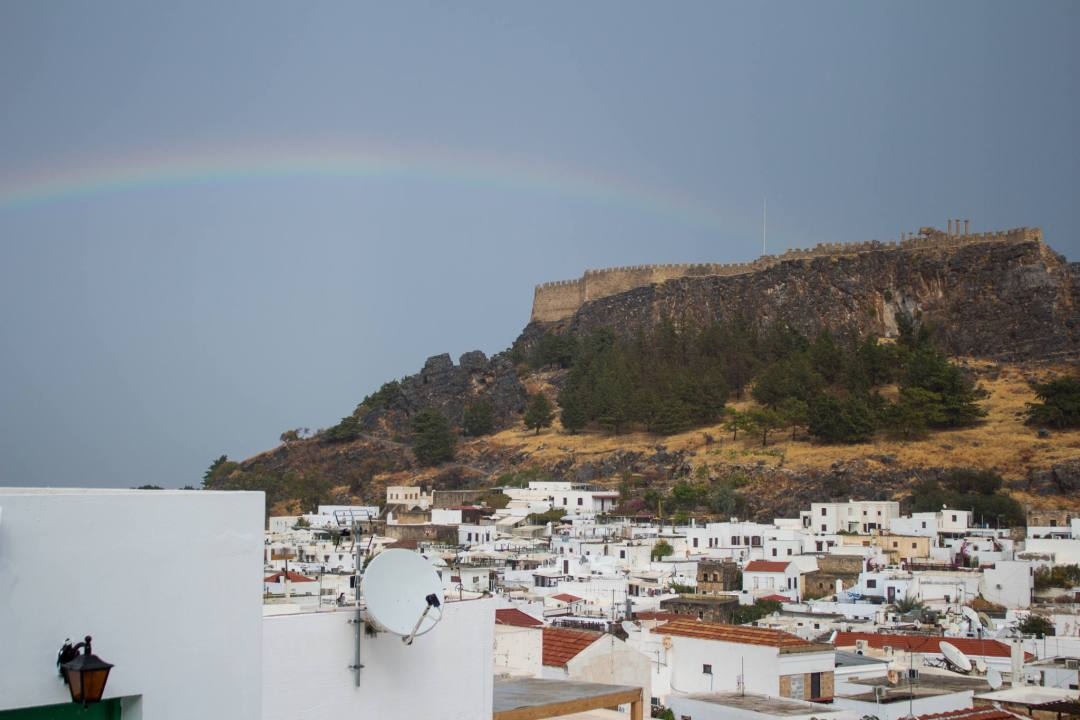rainbow over lindos village and acropolis on rainy day